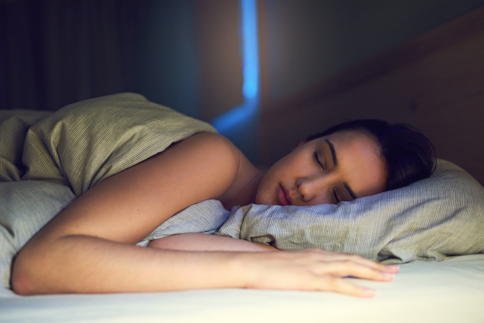 Shot of a young woman sound asleep in her bedroom.