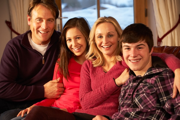 Portrait Of Family Relaxing On Sofa Together Smiling To Camera