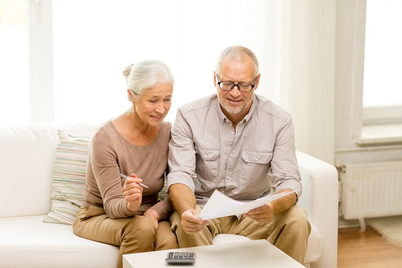 elderly couple looking over a bill