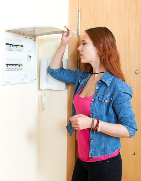 Beautiful woman near power control panel at home