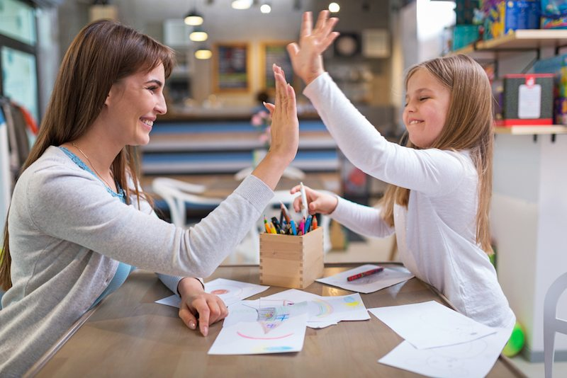 Mother and daughter high-fiving after coloring