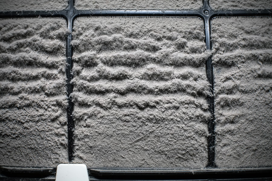 Close up of a dusty home air conditioner filter.