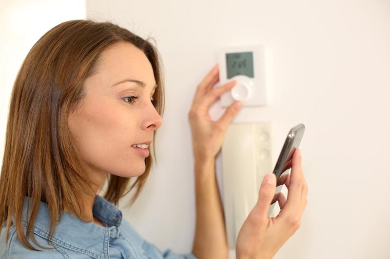 Woman regulating heater temperature