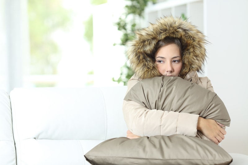 Angry woman warmly clothed in a cold home sitting on a couch. Furnace blowing cold air problem in her home.