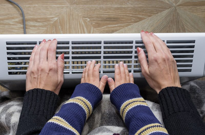 Mother and son heating up a hand in front of an electric heater. Modern electric heater