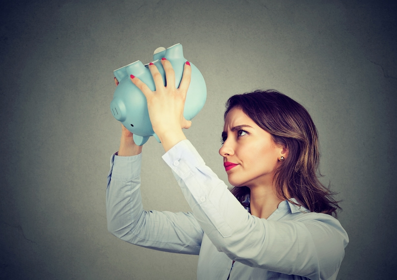 Young worried woman with empty piggy bank