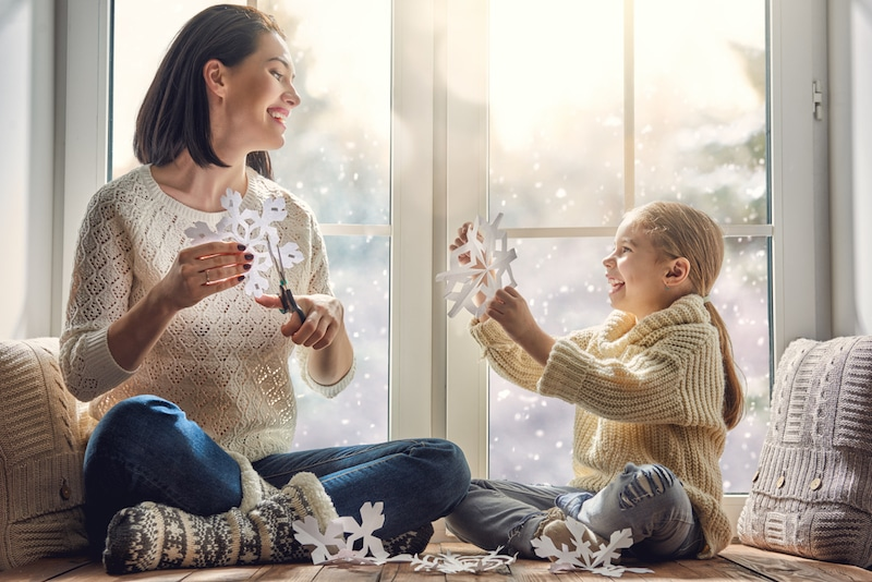 Happy loving family sitting by the window and making paper snowflakes for decoration windows. Mother and child creating decorations. A new furnace is needed in their home.