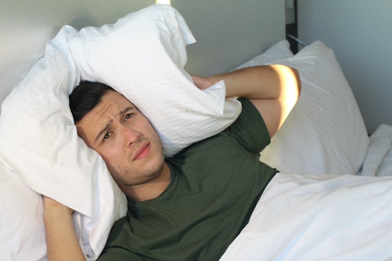 Frustrated man covering his ears with pillow.