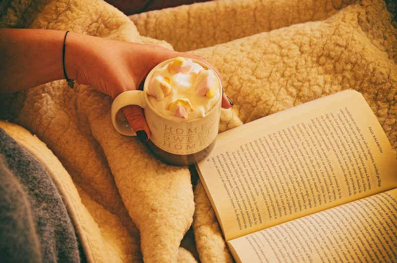 A person drinking hot chocolate while reading a book about furnace filters in Hudson