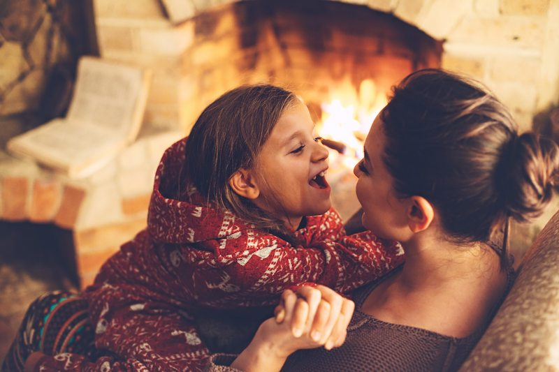 Mom and daughter sit by the fireplace